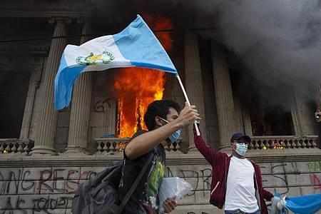 Ein Demonstrant schwenkt vor dem brennenden Kongress die Nationalfahne. Foto: Oliver De Ros/AP/dpa