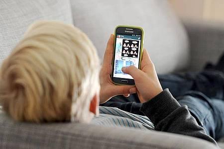 Was machst du da?Wenn Kinder mit dem Smartphone hantieren, wollen Eltern gerne sicher sein, dass der Nachwuchs nicht einfach so die App wechselt. Foto: Tobias Hase/dpa