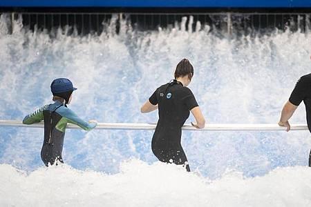 Anfänger surfen im Berliner Wellenwerk zunächst mit Haltestange. Foto: Florian Schuh/dpa-tmn