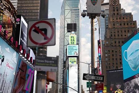 Am Times Square in New York weisen elektronische Plakatwände auf Hygiene- und Abstandsregeln hin. Foto: Michael Nagle/XinHua/dpa