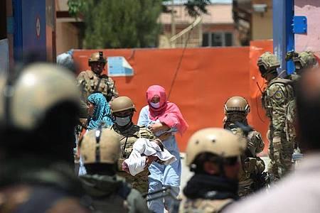 Sicherheitskräfte und Gesundheitspersonal mit Schutzmasken tragen Babys aus einem Krankenhaus nach einem Anschlag in Kabul. Foto: Rahmatullah Alizadah/XinHua/dpa