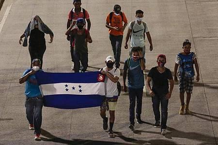 Menschen tragen eine Fahne von Honduras und gehen in der Hoffnung, zukünftig die USA zu erreichen, einen Highway entlang. Foto: Uncredited/AP/dpa