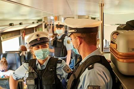 Beamte der Bundespolizei und Mitarbeiter der DB Sicherheit kontrollieren in einem ICb die coronabedingte Maskenpflicht. Foto: Annette Riedl/dpa