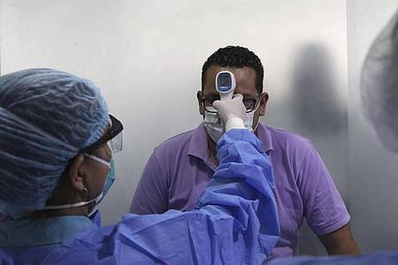 In einer medizinischen Station in Perus Hauptstadt Lima wird die Körpertemperatur eines Mannes gemessen. Foto: Martin Mejia/AP/dpa