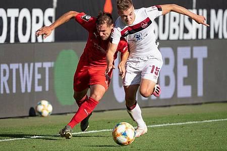 Michael Heinloth von Ingolstadt (l) und Fabian Nürnberger von Nürnberg im Kampf um den Ball. Foto: Matthias Balk/dpa