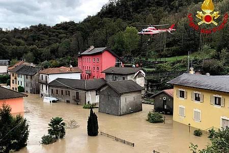 Ein Feuerwehrhubschrauber überfliegt die überschwemmte Stadt Ornavasso in der norditalienischen Region Piemont. Foto: -/Vigili del Fuoco/dpa