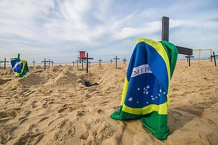 Protestaktion am berühmten Copacabana-Strand inRio de Janeiro: Eine NGO hat Grabkreuze und brasilianische Flaggen aufgestellt. Foto: Ellan Lustosa/ZUMA Wire/dpa