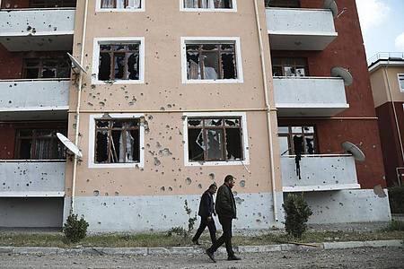 Zwei Männer gehen nach einem Beschuss der armenischen Artillerie an einem beschädigten Gebäude vorüber. Foto: Aziz Karimov/AP/dpa