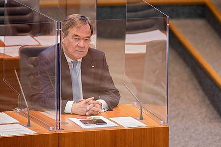 NRW-Ministerpräsident Armin Laschet sitzt im Plenum des Düsseldorfer Landtags in einer Plexiglas-Box. Foto: Rolf Vennenbernd/dpa