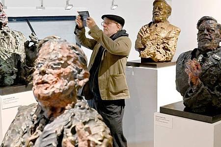 Der Künstler Rainer Fetting zwischen Helmut-Schmidt-Skulpturen. Foto: Carsten Rehder/dpa