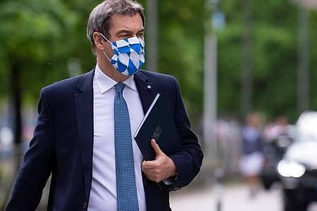 Bayerns Ministerpräsident Markus Söder mit Mundschutz auf demWeg zu einer Pressekonferenz. Foto: Sven Hoppe/dpa