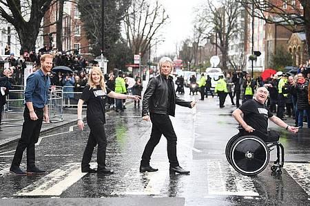 Jon Bon Jovi und Prinz Harry mit Mitgliedern des Invictus-Games-Chors auf dem berühmten Zebrastreifen vor den Abbey Road Studios. Foto: Victoria Jones/PA Wire/dpa