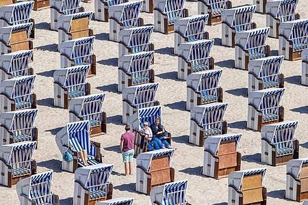 Erste Urlauber sitzen in Strandkörben am Ostseestrand in Warnemünde. Foto: Jens Büttner/dpa-Zentralbild/dpa