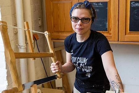 Die angehende Tischlerin Marly Konefka hält eine Gestellsäge, die zu den ursprünglichen Werkzeugen der Tischler gehört. Foto: Catherine Waibel/dpa-tmn