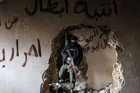 Ein bewaffneter Kämpfer der Miliz Haiat Tahrir al-Scham inspiziert ein beschädigtes Haus. Foto: Anas Alkharboutli/dpa/Archiv
