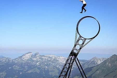 Der Akrobatikkünstler Ramon Kathriner bei der «Glacier 3000 Air Show» auf einem «Todesrad». Foto: Laurent Gillieron/KEYSTONE/dpa