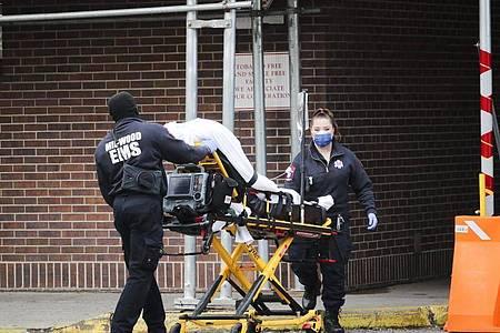 Mitarbeiter des Gesundheitswesens schieben einen Patienten in das Brooklyn Hospital Center in Brooklyn. In der außer Kontrolle geratenen Corona-Pandemie in den USA könnten in den kommenden Monaten nach Modellrechnungen weitere Zehntausende Menschen sterben. Foto: Wang Ying/XinHua/dpa