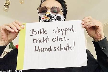 """Ein Mann mit Mundschutz hält in einem Ausschnitt aus der """"Corona-Rolle"""" ein Schild mit der Aufschrift """"Bitte skyped nicht ohne Mundschutz"""" hoch. Foto: --/EchtzeitExperiment/dpa"""