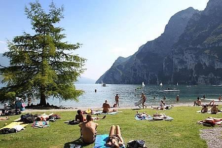 Touristen und Einheimische nehmen am Strand von Riva del Garda ein Sonnenbad. Foto: picture alliance / dpa
