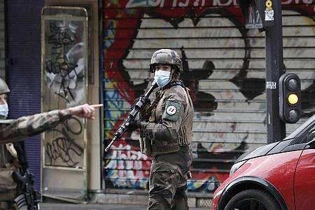 Polizisten patrouillieren nach der Messerattacke in der Nähe der ehemaligen Redaktionsräume von «Charlie Hebdo». Foto: Thibault Camus/AP/dpa