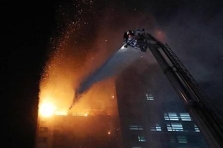 Feuerwehrleute versuchen, den Brand in einem Hochhaus zu löschen. Foto: -/YNA/dpa