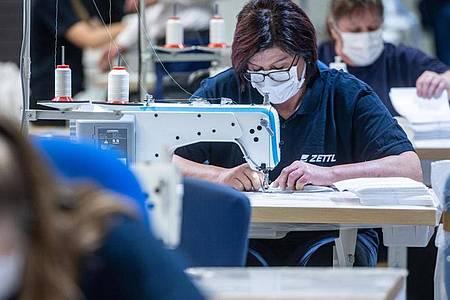 Ein Automobilzulieferer in Bayern hat auf die Produktion von Mundschutzmasken umgestellt. Foto: Armin Weigel/dpa