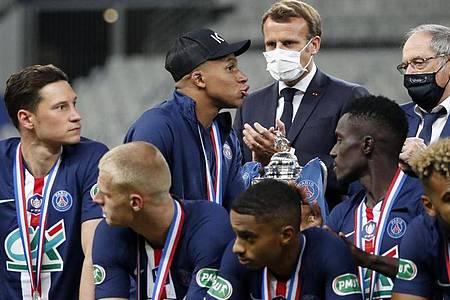 Musste die Glückwünsche von Präsident Emmanuel Macron (M) zum PSG-Pokalsieg auf Krücken entgegennehmen: Kylian Mbappé (3.v.l.). Foto: Francois Mori/AP/dpa