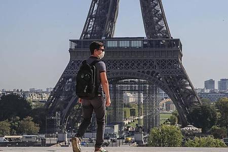 Ein Passant geht mit Mundschutzmaske über den Place du Trocadéro, während im Hintergrund ein Teil des Eiffelturms zu sehen ist. Foto: Michel Euler/AP/dpa