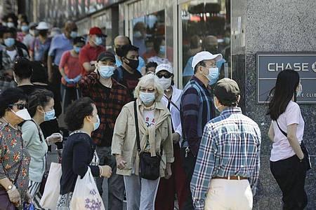 Menschen mit Masken warten im New Yorker Stadtbezirk Queens vor dem Eingang einer Bank. Foto: Frank Franklin Ii/AP/dpa
