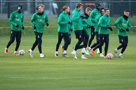 Die Spieler von Borussia Mönchengladbach laufen sich für das Training warm. Foto: Marius Becker/dpa
