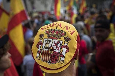 Ein Mann mit einer Mütze auf der das spanische Wappen zu sehen ist, nimmt an einer Demonstration, die während des Nationalfeiertags in Spanien stattfindet, teil. Foto: Santi Palacios/AP/dpa