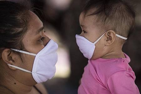 Mutter und Kind mit Mundschutz: Die Forscher fanden keinen Unterschied in der Viruslast zwischen verschiedenen Altersgruppen. Foto: Rodrigo Abd/AP/dpa/Symbolbild