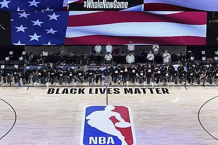 Die Spieler der New Orleans Pelicans und Utah Jazz knien bei der Nationalhymne gemeinsam vor einem «Black Lives Matter»-Schriftzug. Foto: Ashley Landis/Pool AP/dpa