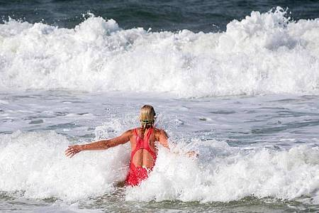 In die Wellen zu springen, macht Spaß - im Meer lauern aber auch gefährliche Strömungen. Foto: Daniel Bockwoldt/dpa/dpa-tmn