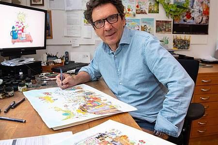 Der geistige Vater der Olchis, der Kinderbuchautor und Illustrator Erhard Dietl, am Schreibtisch. Foto: Sven Hoppe/dpa