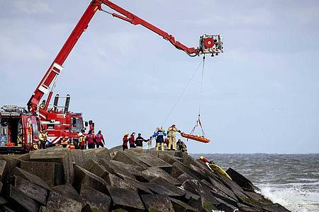 """Rettungskräfte bergen eine Leiche, die sie bei der erneuten Suche nach den vermissten Wassersportlern im Noordelijk Havenhoofd gefunden haben. Foto: """"sem Van Der Wal""""/ANP/dpa"""