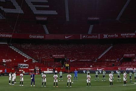 Spieler des FCSevilla und Real Betis Sevilla legen eine Schweigeminute für die Coronavirus-Todesopfer ein. Foto: Str/AP/dpa
