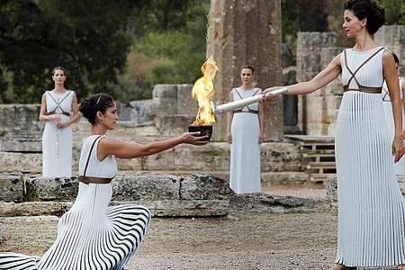 Eine als Hohepriesterin verkleidete Schauspielerin (2.v.r) entzündet 2017 in Olympia eine Fackel an einer Schale mit Feuer. Foto: Alkis Konstantinidis/POOL/dpa