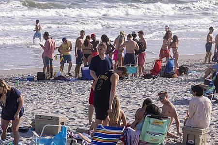 Ungeachtet der Ansteckungsgefahr durch das neuartige Coronavirus vergnügen sich Dutzende Studenten an einem Strand an der US-Ostküste. Foto: Jason Lee/The Sun News/AP/dpa