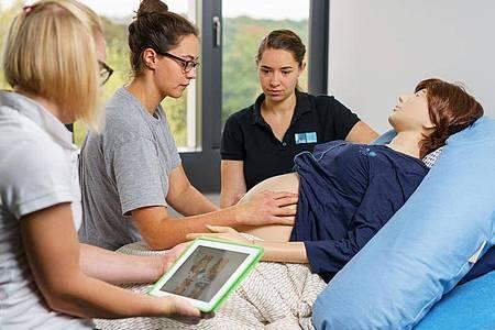 Im Skills-Lab der HSG Bochum gibt es Patientensimulatoren: Damit können angehende Hebammen Situationen aus ihrem Berufsalltag - wie hier zum Beispiel die Leopold?schen Handgriffe - stressfrei einüben. Foto: Volker Wiciok/hsg Bochum/dpa-tmn