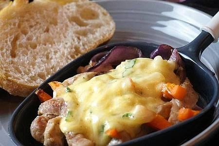 Das marinierte Zwiebelfleisch gart im Raclette-Pfännchen zunächst 5 Minuten, erst dann kommt die Käse-Mascarpone oben drauf und wird nochmals 5 Minuten überbacken. Foto: Doreen Hassek/dekoreenberlin.blogspot.com/dpa-tmn