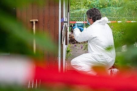 Ein Polizeibeamter der Spurensicherung kniet in der Kleingartenkolonie vor der Laube des vermutlichen Haupttäters. Foto: Guido Kirchner/dpa