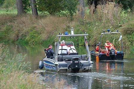 Boote der Wasserschutzpolizei und der Deutschen Lebensrettungsgesellschaft (DLRG) fahren auf der Unstrut. Foto: Sebastian Willnow/dpa-Zentralbild/dpa