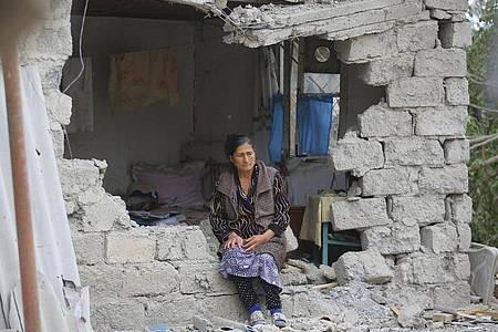 Eine Frau sitzt nach einem Beschuss der armenischen Artillerie inmitten der Trümmer ihres Hauses. Foto: Aziz Karimov/AP/dpa