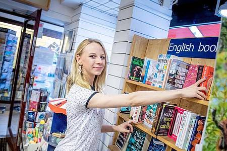 Deutsch oder Englisch? Als angehende Buchhändlerin muss Sophie Schmale lernen, sich auf die Lesegewohnheiten verschiedener Kunden einzustellen. Foto: Zacharie Scheurer/dpa-tmn