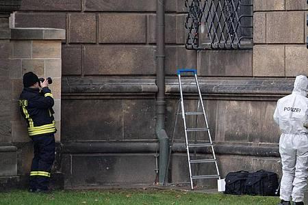 Einsatzkräfte der Polizei stehen im Bärengarten neben dem durchtrennten Gitterfenster des Grünen Gewölbes am Residenzschloss. Knapp ein Jahr nach dem Kunstraub im Dresdner Grünen Gewölbe hat die Polizei in Berlin drei Tatverdächtige festgenommen. Foto: Sebastian Kahnert/dpa-Zentralbild/dpa