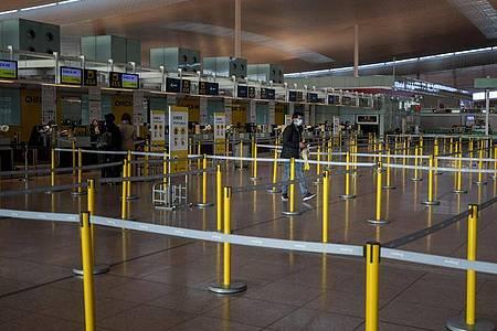 Ein Mann mit Mundschutzmaske im leeren Terminal eines Flughafens. Foto: Emilio Morenatti/AP/dpa