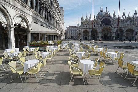 Leere Stühle und Tische vor einem Restaurant auf dem Markusplatz. Foto: Anteo Marinoni/LaPresse/AP/dpa