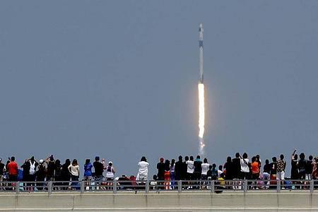 Zuschauer beobachten den Start der «Falcon 9»-Rakete vom Weltraumbahnhof Cape Canaveral. Foto: Charlie Riedel/AP/dpa