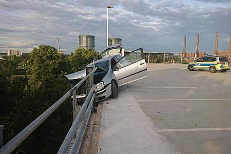 Das Auto hängt in der Sicherungsplanke auf einem Parkhausdeck in Wolfsburg. Foto: -/Polizei Wolfsburg/dpa